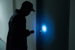 Male Security Guard With Flashlight. Standing In Front Of Door Stock Images