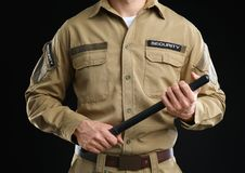 Male security guard with police baton. On dark background Royalty Free Stock Photography