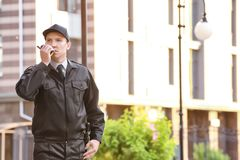 Male security guard with portable radio,. Outdoors Royalty Free Stock Image