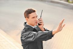 Male security guard with portable radio,. Outdoors Stock Photos