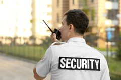 Male security guard with portable radio,. Outdoors Stock Images
