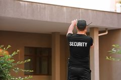 Male security guard with portable radio,. Outdoors Royalty Free Stock Photography