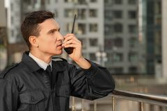 Male security guard with portable radio,. Outdoors Royalty Free Stock Images