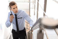 Handsome male security guard with portable radio transmitter indoors. Male security guard with portable radio transmitter indoors Royalty Free Stock Photo