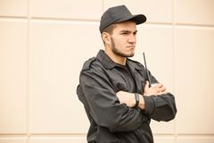 Male security guard with portable radio transmitter. Near light wall Royalty Free Stock Photo