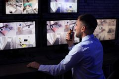 Male security guard with portable transmitter monitoring home cameras. Indoors at night stock photography
