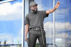 Male security guard showing stop gesture. Near big modern building Royalty Free Stock Photography