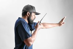 Male security guard showing stop gesture. While using portable radio, on white background Royalty Free Stock Images
