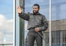 Male security guard showing stop gesture. Near big modern building Royalty Free Stock Image