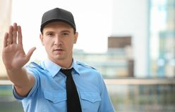Male security guard showing stop gesture,. Outdoors Royalty Free Stock Images