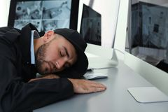 Male security guard sleeping. At workplace indoors stock images