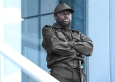 Male security guard standing near big   building. Male security guard standing near big modern building Stock Photos