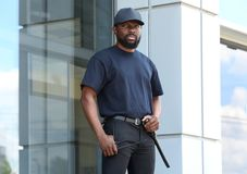 Male security guard standing. Near big modern building Royalty Free Stock Photos