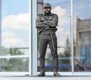Male security guard standing near building. Male security guard standing near big modern building Royalty Free Stock Images