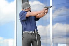 Male security guard taking aim. Near big modern building Stock Photography