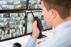 Male Security Guard Talking On Walkie-talkie. Close-up Of Male Security Guard Talking On Walkie-talkie While Monitoring Multiple CCTV Footage Stock Photos