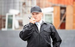Male security guard using portable radio. Outdoors Royalty Free Stock Photography