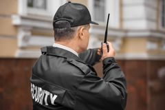 Male security guard using portable radio. Outdoors Stock Image