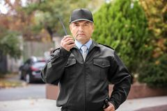 Male security guard using portable radio. Outdoors Royalty Free Stock Images