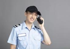 Security guard using portable radio transmitter. Male security guard using portable radio transmitter royalty free stock image