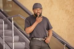 Male security guard using portable radio transmitter. Indoors Royalty Free Stock Images