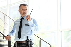 Male security guard using portable radio transmitter. Indoors stock photography