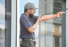 Male security guard using portable radio transmitter. Near big modern building Stock Images