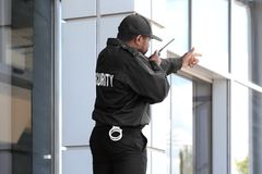 Male security guard using portable radio transmitter. Near big modern building Royalty Free Stock Photo