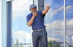 Male security guard using portable radio transmitter. Near big modern building Stock Photo
