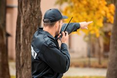 Male security guard using portable radio transmitter. Outdoors Royalty Free Stock Photo