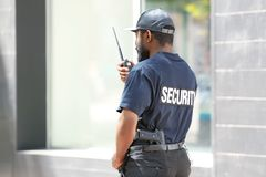 Male security guard using portable radio transmitter. Outdoors Stock Images