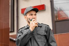 Male security guard using portable radio transmitter. Near building outdoors Royalty Free Stock Image