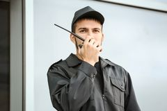 Male security guard using portable radio transmitter. Near building outdoors Stock Photos