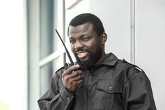 Male security guard using portable radio transmitter. Outdoors Stock Photo