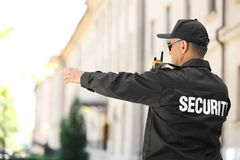 Male security guard using portable radio transmitter. Outdoors stock image