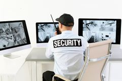 Free Male Security Guard With Portable Transmitter Monitoring Home Cameras Royalty Free Stock Photo - 129575905