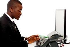 Male sekreterare för sidosikt som skrivar på tangentbordet Arkivbild