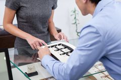 Male selecting engagement ring. At jeweler's shop. Concept of wealth and luxurious life Stock Image