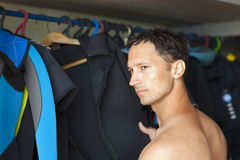 Male selects diving neoprene suit. Closeup studio shot Stock Photos