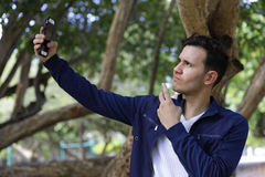Male selfie. Male model posing for a selfie in the park Royalty Free Stock Photo
