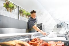 Male seller adding ice to fridge at fish shop. Food sale, small business and people concept - male seller with scoop adding ice to fridge at fish shop Royalty Free Stock Photo