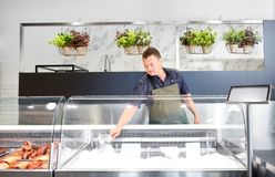 Male seller adding ice to fridge at fish shop. Food sale, small business and people concept - male seller with scoop adding ice to fridge at fish shop Royalty Free Stock Images