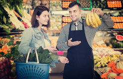 Male seller assisting in buying. Male shopping assistant helping customer to buy fruit and vegetables in grocery shop Stock Photography