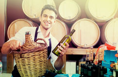 Male seller with bottle in hands in cellar. Smiling male seller wearing apron with bottle in hands in cellar Royalty Free Stock Image