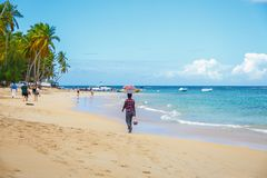 Male seller on the Caribbean beach. Local Salesman with goods on the head on the caribbean beach. Punta Cana, Dominican Republic Royalty Free Stock Photo