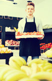 Male seller carrying box of persimmons. Young male seller carrying box of persimmons in the grocery shop Stock Image