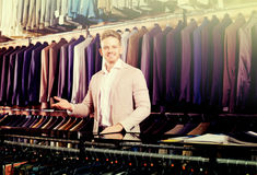 Male seller demonstrating numerous suits. Happy male seller demonstrating numerous suits in men's cloths store Stock Photo