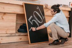 Male seller drawing fifty percent discount sign on chalkboard. Young male seller drawing fifty percent discount sign on chalkboard Royalty Free Stock Image