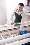 Male seller in fish store. Male seller near display with frozen fish Stock Images