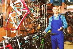 Male seller fixing bike in bike store. Cheerful smiling man seller wearing uniform fixing bike in bike store Stock Photo